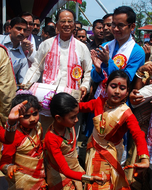 Assam Chief Minsiter Tarun Kumar Gogoi beats a dhol while children perform Bihu