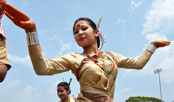 Youth in traditional Assamese attire perform Bihu