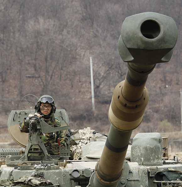 A South Korean soldier rides on a self-propelled artillery vehicle during a military exercise against North Korea's possible attack near the demilitarised zone separating the two Koreas in Paju, about 45 km north of Seoul, April 13