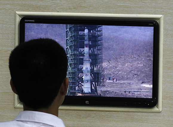A North Korean scientist looks at a monitor showing the Unha-3 rocket on a launch pad, at a control centre on the outskirts of Pyongyang