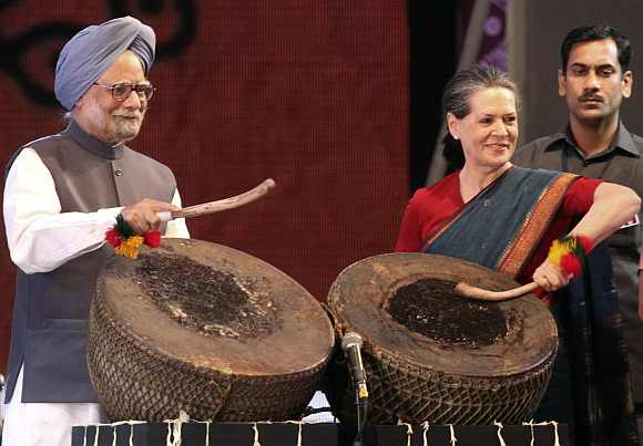 Prime Minister Manmohan Singh and Congress chief Sonia Gandhi play a folk drum